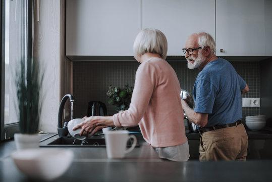 Elder couple enjoying to make household duties