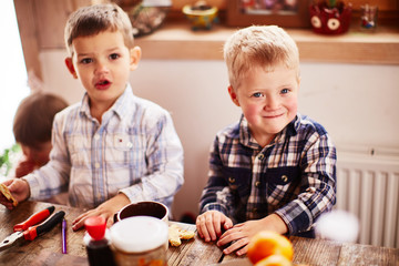 Two young boys sit at the table and rejoice