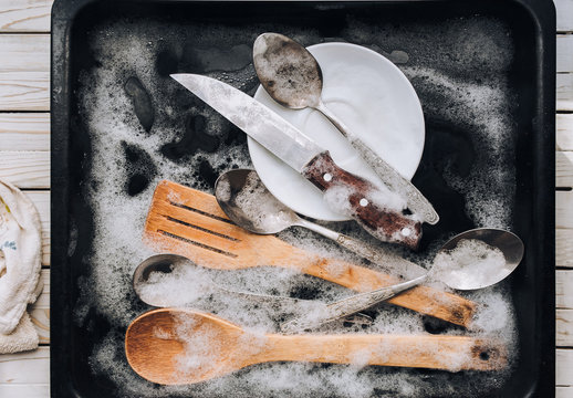 A white plate, a knife, wooden kitchen spatulas and spoons in the detergent foam on a black oven-tray. Washing dishes concept.Top view.