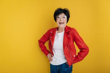 Waist up of elderly woman in red jacket smiling in studio