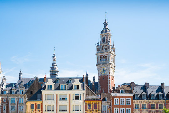 tower of Chamber of commerce, buildings at central town square in Lille, France. Against blue sky. space for text
