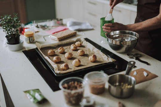 Close up of pastry on the sheet pan and person taking cream