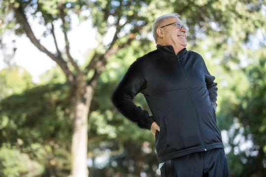 Uomo anziano con maglia blu sente un forte dolore ala schiena