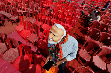 A supporter of India's ruling Bharatiya Janata Party (BJP) wearing a mask of Prime Minister Narendra Modi checks his mobile phone as he attends an election campaign rally being addressed by Modi in Meerut