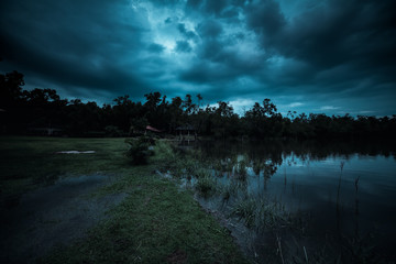 Wall Mural - moonlight shines behind a cloudy at night over tranquil lake