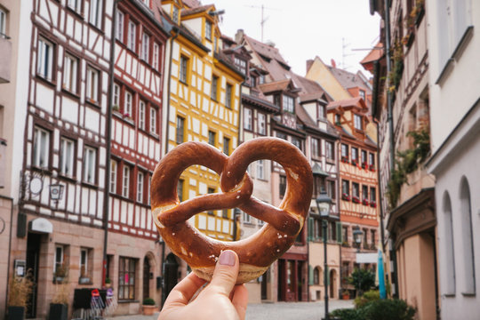 A girl holds in her hand a traditional German pretzel on the background of a beautiful architecture or street in Nuremberg in Germany.