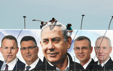 Labourers work on hanging up a Likud election campaign banner depicting Israeli Prime Minister Benjamin Netanyahu with his party candidates, in Jerusalem