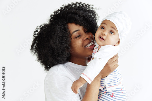 Closeup portrait of beautiful african woman holding on hands her little daughter on white background. Family, love, lifestyle, motherhood and tender moments concepts. Mother's day concept or