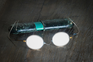 Old broken glasses with a paper case on the background of a wooden table. Glasses sparkle with reflected light. The case is slightly blurred, as if looking without glasses