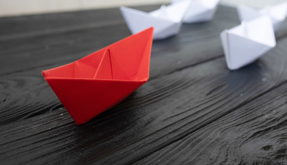 Leadership concept. Red leader paper ship leading among white on black background.
