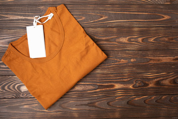 Top view of color T-Shirt on old wood plank background
