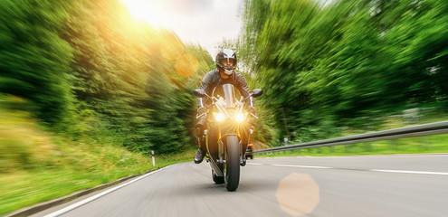 motorcycle driving on empty road at sunset. adventure freedom of single driver motorbike on highway. copy space for individual text on the right.