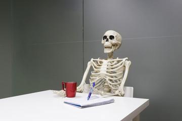 esqueleto en oficina trabajando y muerto de aburrimiento