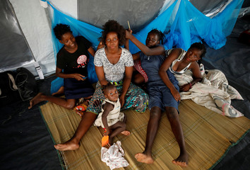 Women braid hair in a tent at a camp for people displaced in the aftermath of Cyclone Idai in Beira