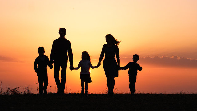 Silhouettes of happy family holding the hands in the meadow during sunset.