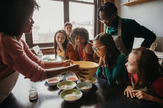 Teacher showing ingredients to students on table in cooking class