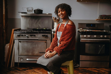Portrait of smiling female student with curly hair sitting on stool against appliances in cooking class