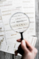 """A magnifying glass enlarging the words, """"traveling"""" """"were to fly away"""" on a page"""