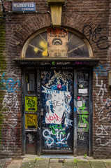 The door to the entrance of the house is painted graffiti
