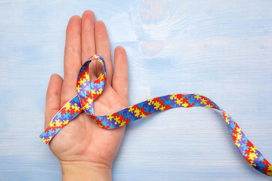 World Autism awareness and pride day with Puzzle pattern ribbon on hand