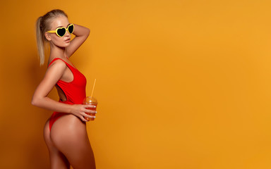 Lovely young female in swimwear and sunglasses holding glass of fresh drink while standing on yellow, orange hot background.