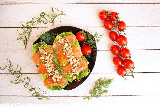 Kanapki z wędzonym łososiem i kiełkami otoczone pomidorami, gałązkami rozmarynu i kopru