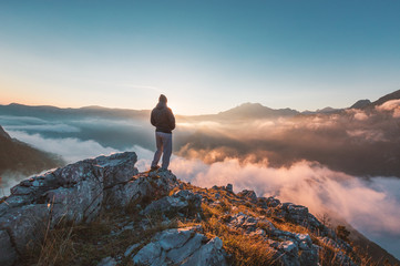 Successful hiker enjoying at top of mountain above clouds