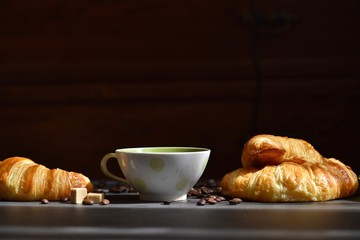 Coffee composition. Cup of coffee, croissants, sugar slices on a dark background