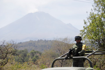 A soldier keeps watch atop a military vehicle while checking an evacuation route after Mexican authorities raised the alert level for the Popocatepetl volcano (in the background) following an increase in its activity, in Santiago Xalizintla