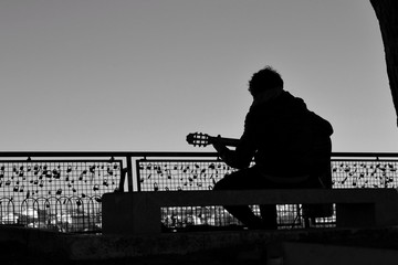 Musician playing the guitar on a viewpoint in Lisbon