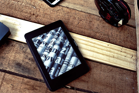 Kindle over a wood surface surrounded by electronic devices
