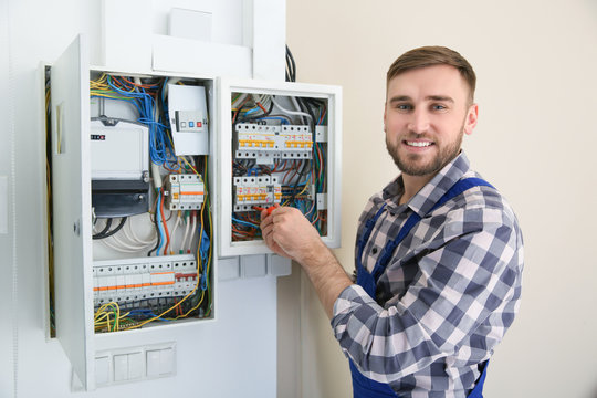 Electrician repairing fuse box with screwdriver indoors