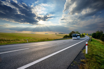 Fotobehang - White bus traveling on the asphalt road in rural landscape at sunset with dramatic clouds