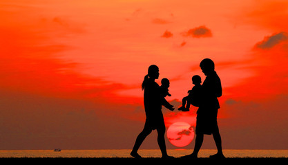 silhouette happy  family on the beach at  sunrise time