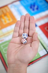 Man is showing two dice in hand.