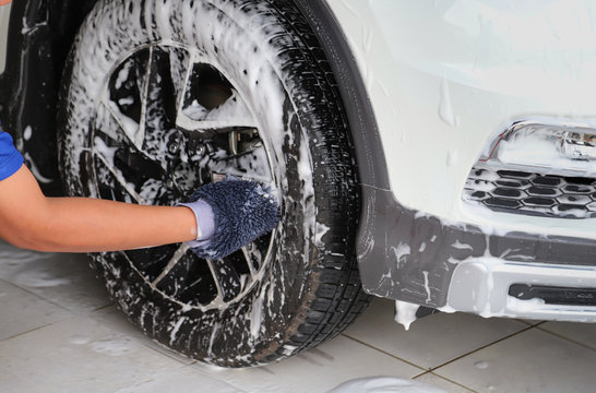 Closeup of front wheel of white car washing, rubbing and cleaning by man's hand with glove.