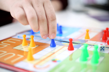 Picture of ludo board game with hand playing ludo.