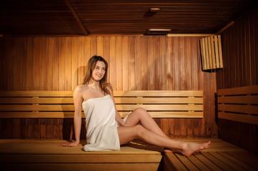 Fototapeta close up photo of  a beautiful woman wearing a white towel in a wooden sauna