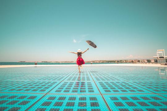 Happy woman traveler dances on outdoor disco floor in Zadar, Croatia.