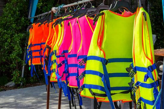 many colorful life jacket or life vest hanging on a clothesline