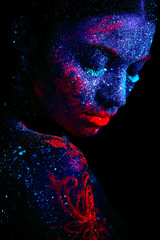 Profile portrait of a beautiful girl alien. Ultraviolet body art blue night sky with stars and pink jellyfish