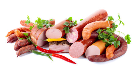 Fototapete - Different sausages and smoked meats with parsley and pepper on white background .