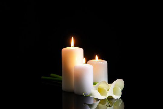 Burning candles and flowers on dark background