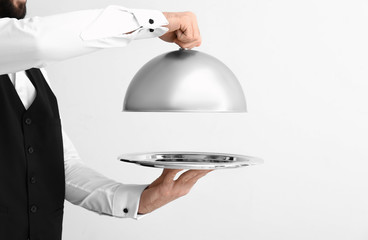 Waiter with tray and cloche on light background