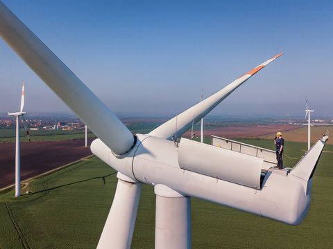 Aerial shot of a worker standing on the top of a wind turbine.