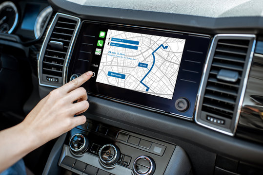 Touching a monitor with navigation map of the modern car, close-up view