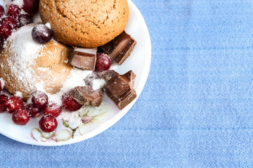 Oatmeal cookies with berries and chocolate on a plate - sweet still life