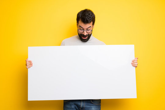 Man with beard and turtleneck holding a placard for insert a concept