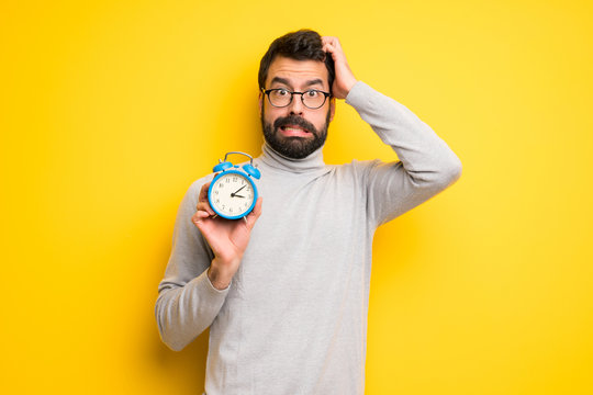 Man with beard and turtleneck restless because it has become late and holding vintage alarm clock