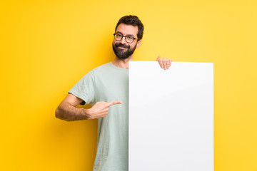 Man with beard and green shirt holding an empty placard for insert a concept Wall mural
